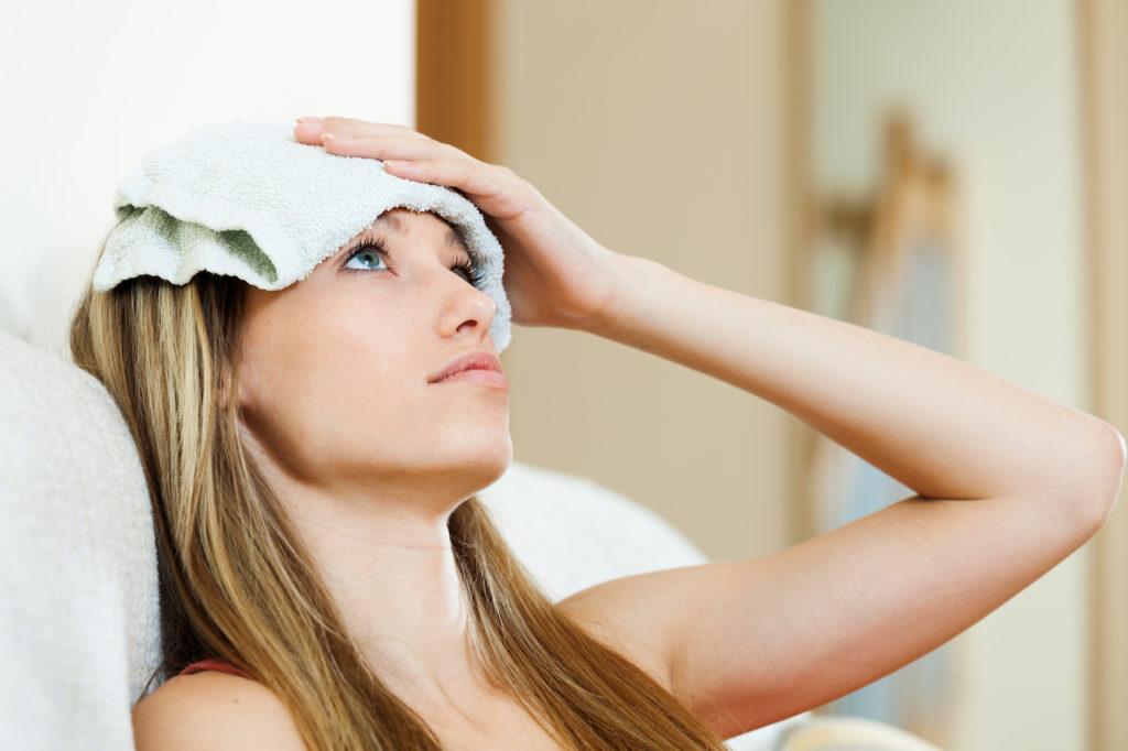 Frau mit kühlendem Tuch auf der Stirn